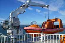 Orange Lifeboat, Rescue Boat Of Ferry Boat Sailing On The Sea With Blue Sky And Coastline In The Background.