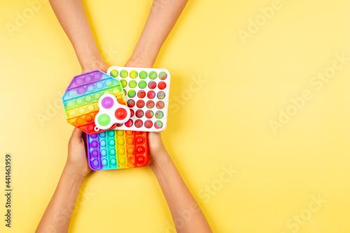 Obraz na plátně Hands holding colorful pop it fidget toys on yellow background