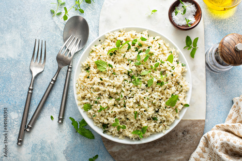 Cauliflower rice with herbs and lemon juice in a white bowl