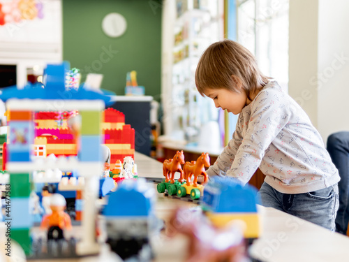 Fotografie, Obraz Toddler plays with colorful toy blocks