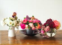 Three Vases Of Fresh Farm Roses On Display