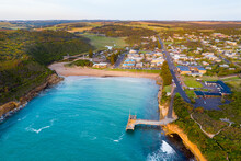 Aerial View Of Coastal Town And Jetty Around A Sheltered Inlet And Beach