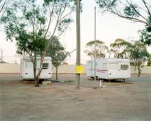 Two Old Caravans Parked In Dusty, Remote Caravan Park