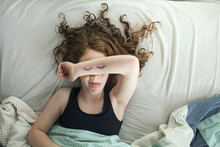 A Girl Laying In Bed Pretending To Sleep From Above