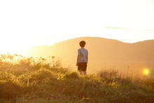 Young Boy Looking Out To Mountains At Sunset