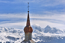 Metal Bell Tower Of A Church In The Shape Of A Bulb On A Snowy Mountain Background