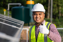 Young Asian Electrical Engineer Standing In Front Of Solar Cell Panels Farm. He Showing Thumbs Up. Solar Generator Power Concept.