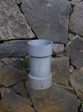 Sewer Pipe Close-up With The Stone Embankment In The Background