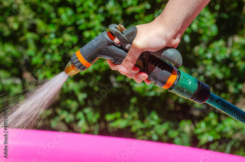 Canvas Print Hand holds a hose with sprayer and watered the plants