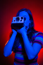 Anonymous Woman Photographing With Retro Instant Camera In Studio