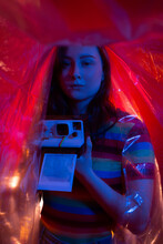 Young Female Photographer Developing Film Images In Darkroom