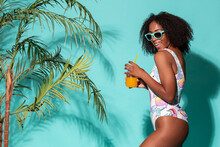 Gorgeous Black Woman In Swimsuit Sipping Refreshing Mocktail In Studio