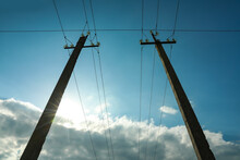 Telephone Poles And Wires Against Blue Sky With Clouds