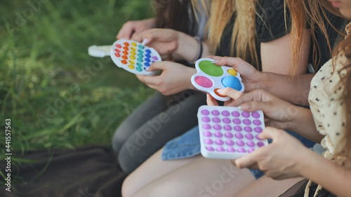 Fotografie, Obraz Girls play with simple dimple relaxing toys and pop it.