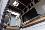 Fototapeta Miasto - Man installing a skylight in a camper van