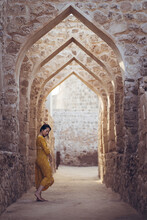 Woman Walking On Arched Passage Of Stone Building
