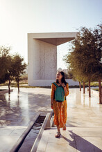 Woman Walking In City Garden With Modern Architecture