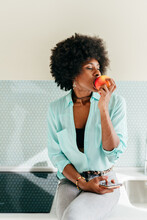 Young Black Woman Eating Apple In Kitchen