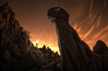 Unrecognizable Traveler Near Huge Stones In Evening