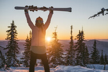 Skier Female Holding Ski Standing On Mountain Top During Sunset, Beautiful Winter Mountains Landscape