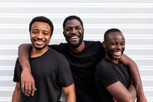 Cheerful Black Male Friends Embracing Near Striped Wall
