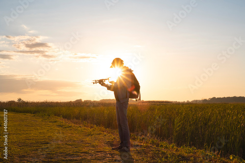 Obraz na plátně Young man holding and setting up a drone at sunset hour against the sunshine