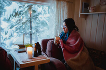 Woman In Blanket With Cup On Sofa Near Window With View Of Trees