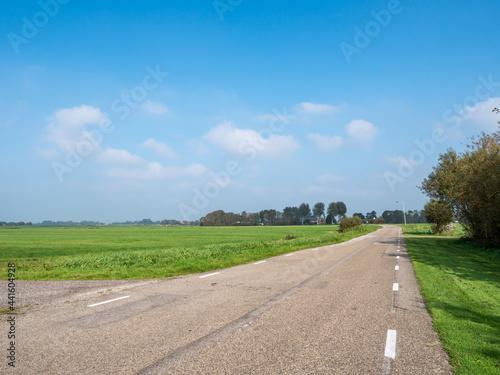 Fotografie, Obraz Polder landscape with empty road near Boornzwaag in Friesland, Netherlands
