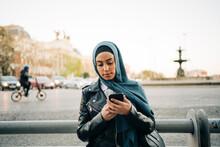 Ethnic Woman In Hijab Using Smartphone In Street