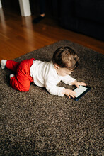 Cute Baby Boy Watching Cartoon On Smartphone On Floor