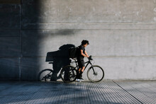 Ethnic Man With Delivery Box And Bicycle On Urban Walkway