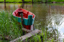 An Old Green And Red Wooden Boat Chained To A Post Near The Shore