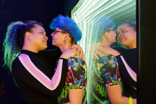 Lesbian Couple Embracing In Moment Of Kiss Against Mirror
