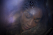 Serene Young Woman With Eyes Closed At Wet Window
