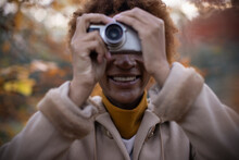 Happy Young Woman Using Digital Camera In Autumn Park
