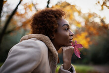 Thoughtful Young Woman With Red Autumn Leaf In Park