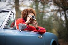 Young Woman Using Digital Camera In Convertible