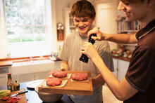 Happy Teenage Boys Preparing Hamburger Patties In Kitchen