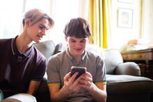 Teenage Boys Using Smart Phone In Living Room