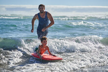 Happy Father And Son Body Boarding In Sunny Ocean Surf