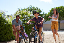 Happy Family Riding Bikes In Sunny Driveway