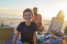 Portrait Cute Boy With Sandy Face On Sunny Beach With Family