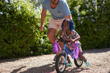 Father Helping Toddler Daughter Riding Bike In Sunny Driveway