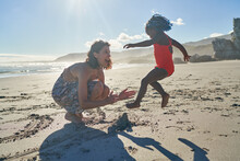 Mother And Playful Toddler Daughter On Sunny Summer Beach