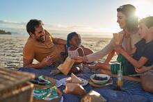 Happy Family Enjoying Picnic On Sunny Summer Beach