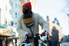 Man In Stocking Cap And Scarf With Bicycle On City Street