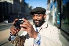 Male Tourist With Digital Camera On Sunny Urban Sidewalk