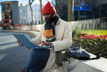 Businessman In Stocking Cap Working At Laptop In City Park