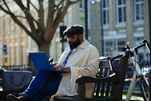Businessman Working At Laptop In City Park