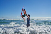 Father Lifting Son With Body Board Above Sunny Ocean Wave
